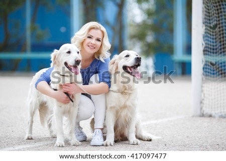 blonde woman with two golden labrador retrievers outdoor. Beautiful girl with her dogs. portrait of girl with pets