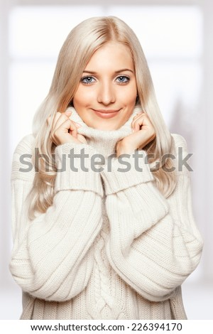 Blonde young beautiful woman dressed in large white cashmere sweater on window background - stock photo
