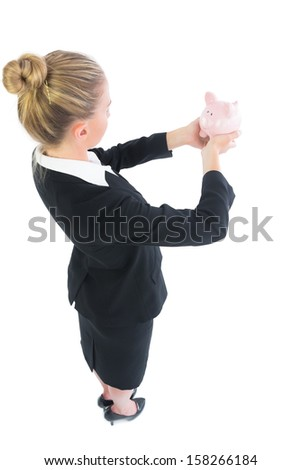 Blonde young businesswoman holding a piggy bank looking at it