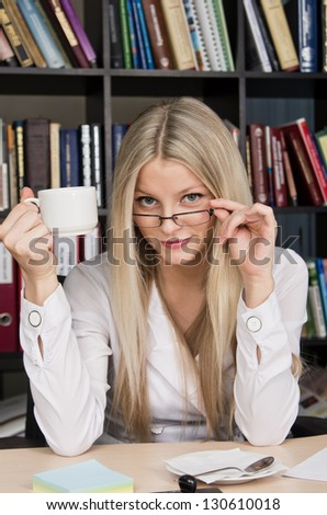 Blonde young girl at office with cup of tea - stock photo