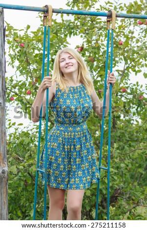 Blonde young girl in feminine silk sundress is standing on handmade swing in summer green garden - stock photo