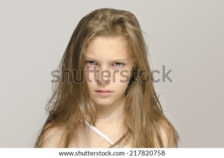 Blonde young girl with messy hair upset and angry. Child having a bad mood and being impatient - stock photo