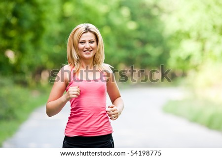 Blonde young lady running through the forest