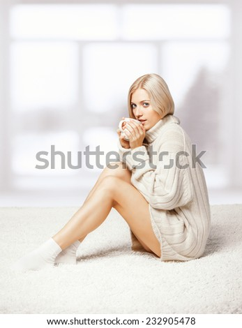 Blonde young woman dressed in large white cashmere sweater and seating on on white whole-floor carpet on window  background drinking a cap of tea - stock photo