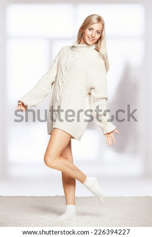 Blonde young woman dressed in long white cashmere sweater on white whole-floor carpet and window background