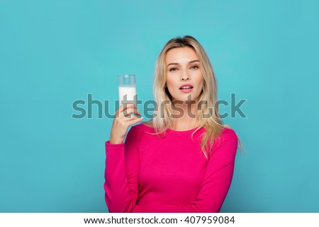 blonde young woman in pink blouse holding a glass of milk on blue background - stock photo