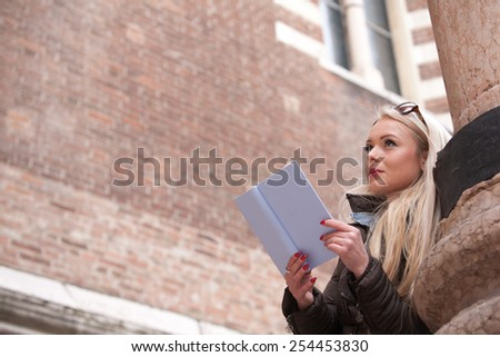 blonde young woman reading a book outdoors maybe in an European city of art