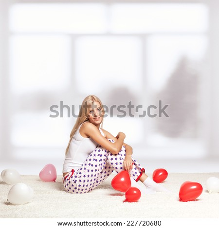 Blonde young woman sitting on white whole-floor carpet and with balloons  near window - stock photo