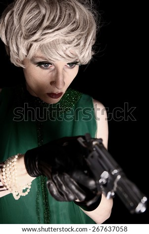 Blonde young woman with a gun - stock photo