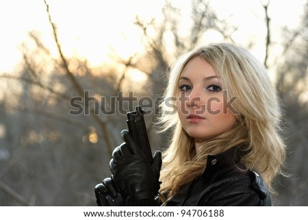 Blonde young woman with a gun at the sunset - stock photo