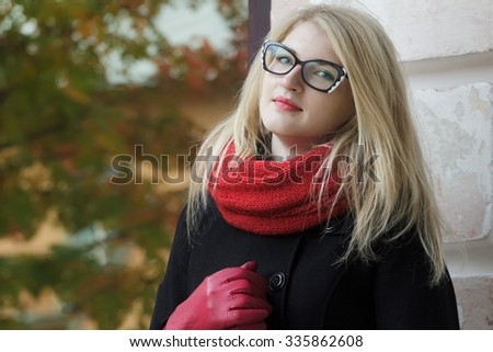 Blonde young woman with cat eye glasses and red leather gloves is leaning at glass door with autumn yellow foliage reflection - stock photo