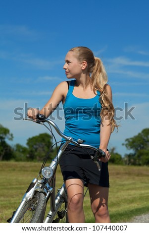 Blonde young woman with her bicyle outside