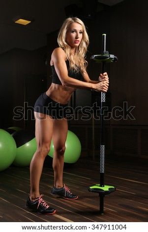 Blondy athletic female doing exercises with barbell in a gym room with green fitness balls.