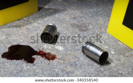 Blood and empty handgun ammo with evidence markers on concrete - stock photo