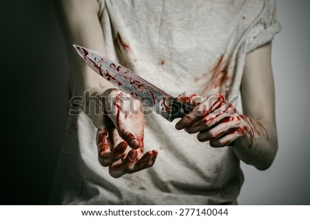 Blood and Halloween theme: man holding a bloody knife in his hand, a bloody murderer - stock photo