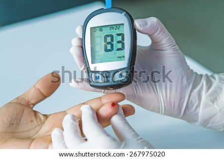 blood glucose meter, the blood sugar value is measured on a finger - stock photo