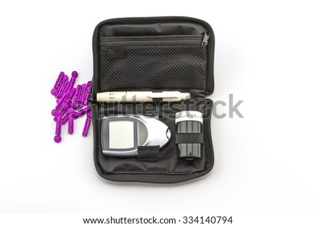 blood glucose meter, the blood sugar value is measured on a finger pack in black case on white background. - stock photo