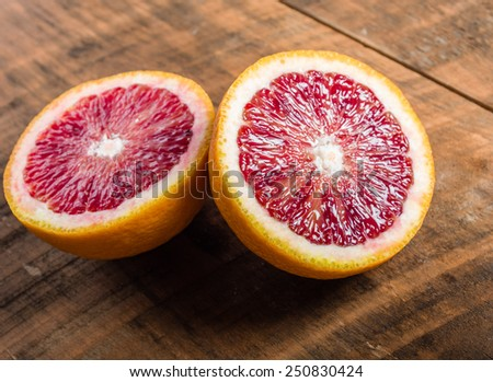 Blood orange halves on a wooden table - stock photo