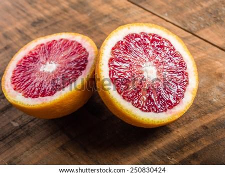Blood orange halves on a wooden table - stock photo