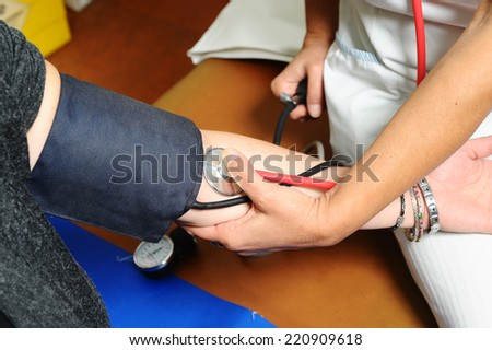 Blood pressure measuring. Doctor measuring patients blood pressure - stock photo