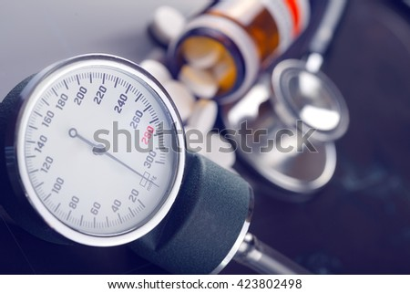 Blood pressure measuring instrument and pills on a dark background