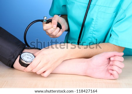 Blood pressure measuring on blue background - stock photo