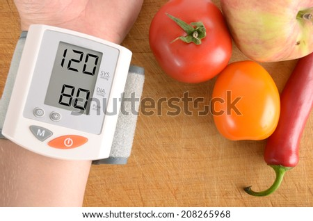 Blood pressure monitor with normal reading concept for illness and heart risk. Pressure gauge with vegetables. The concept shows that healthy food can keep the body in good condition. - stock photo