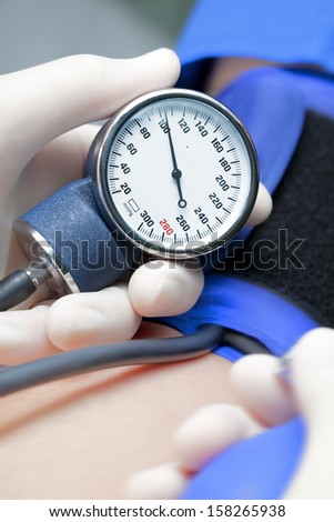 blood pressure of the patient. The doctor measuring blood pressure - stock photo