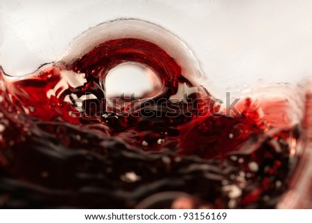 Blood red wine pouring shot from inside the bottle