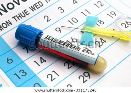 blood sample tube and needle on the bottom of an appointment calendar in lab table / blood tube and needle over a appointment calendar in workbench of lab - stock photo