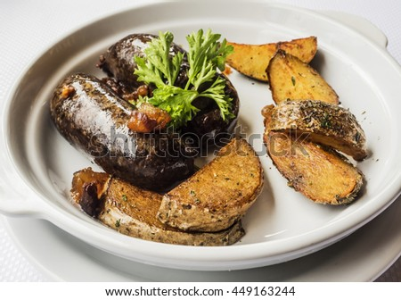 Blood sausage with baked potatoes on a white plate - stock photo
