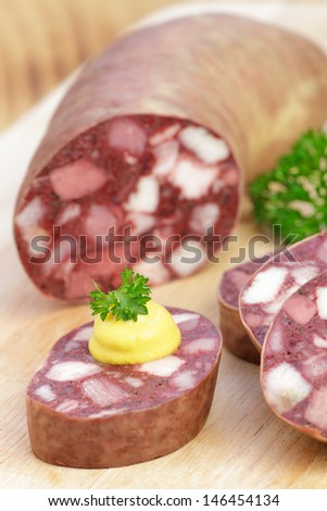 Blood sausage with mustard and parsley on wooden board