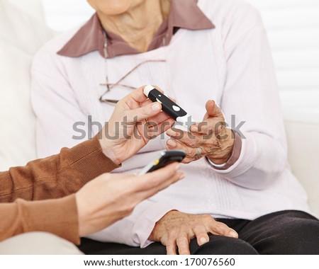 Blood sugar measurement in hand for senior citizen woman - stock photo