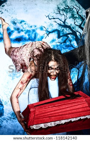Bloodthirsty witch flying at the night cemetery with a coffin. - stock photo