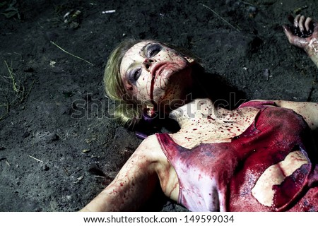 Bloody dead woman lying on the ground - stock photo
