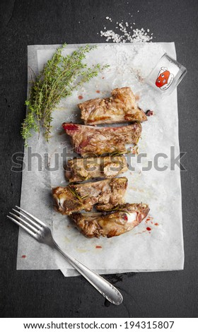 bloody fried pork ribs with herbs, salt and spices on the baking paper and dark background. freshly cooked