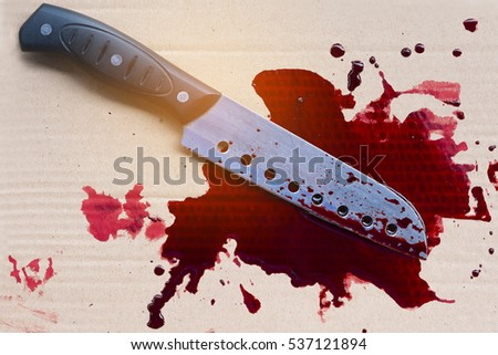 Bloody knife on paper with flowing red blood