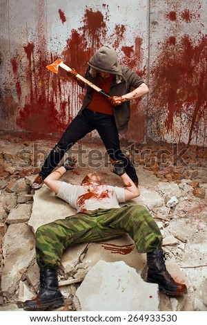 Bloody maniac with the axe is going to kill a victim - stock photo