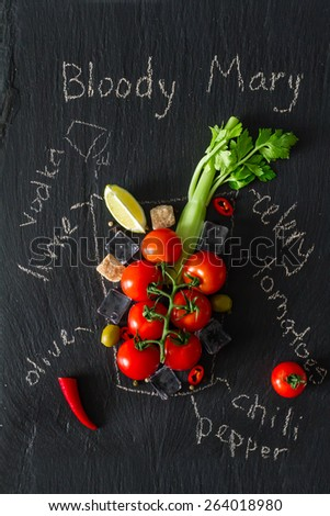 Bloody Mary cocktail ingredients - cherry tomatoes, celery, chili, lemon, sugar, ice on dark stone background with glass painted in chalk, top view - stock photo
