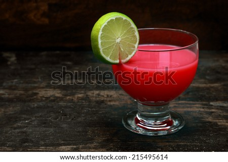 Bloody Mary tomato cocktail garnished with lemon standing on an old wooden bar counter against a dark background with copyspace - stock photo