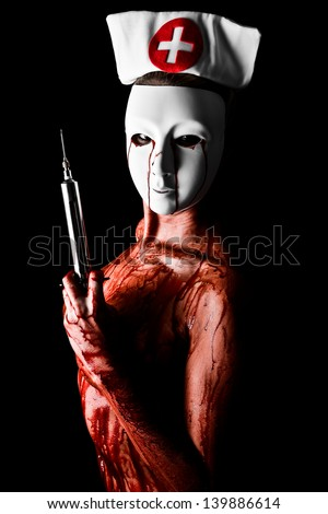 Bloody Nurse holding a large syringe wearing a mask and cap with tears of blood - stock photo