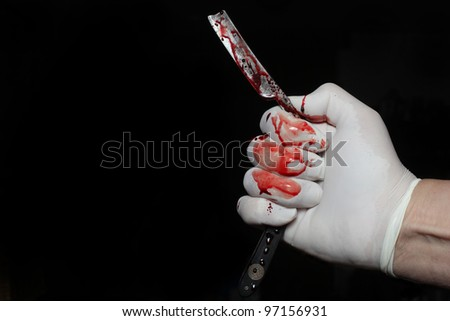 Bloody Razor Against Black Background/Close up of Latex gloved hand holding antique wood handled razor both covered with real blood - stock photo