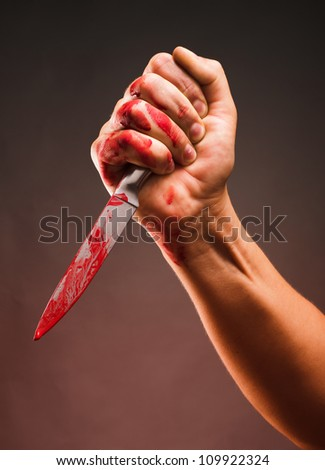 Bloody stabbing. Hand with knife - stock photo