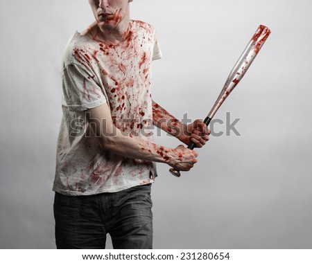 Bloody topic: The guy in a bloody T-shirt holding a bloody bat on a white background - stock photo