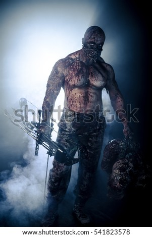 Bloody zombies killer is on the black background of the smoke with a bow. Horror.