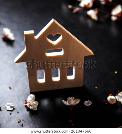 bloom on a black background and a wooden sign with the word house