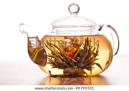 Blooming green tea in glass teapot on a wooden table - stock photo
