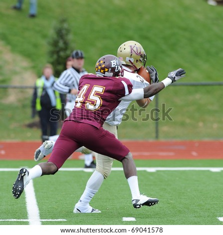 BLOOMSBURG, PA - NOVEMBER 6: Kutztown University receiver Chris McCormick (white jersey) hauls in a long pass in tight coverage in a game on November 6, 2010 in Bloomsburg, PA - stock photo