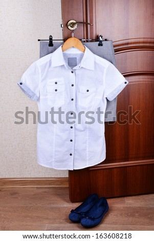 Blouse with skirt hanging on door