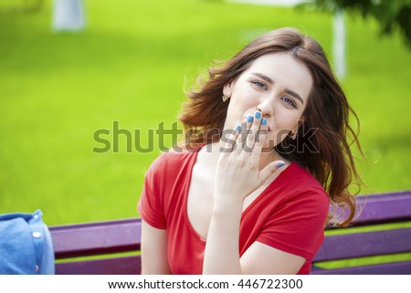Blow kiss, young Caucasian female haired model on the background of summer park - stock photo